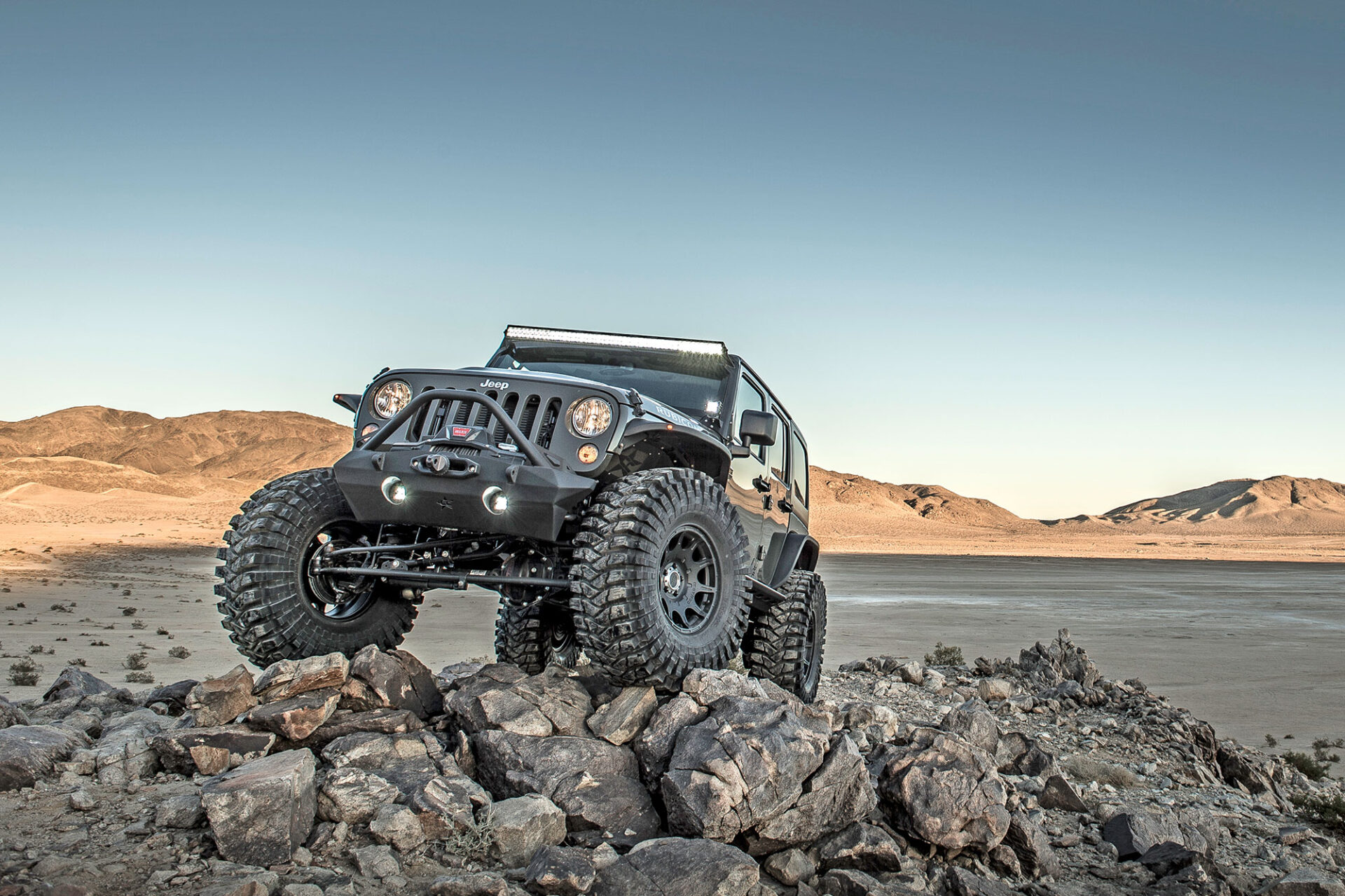 Vehicle outfitted with extreme-off-road Maxxis tires crossing desert rocks.